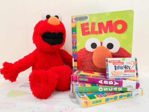 A stuffed Elmo toy next to a stack of Sesame Street books and an OCLS library card