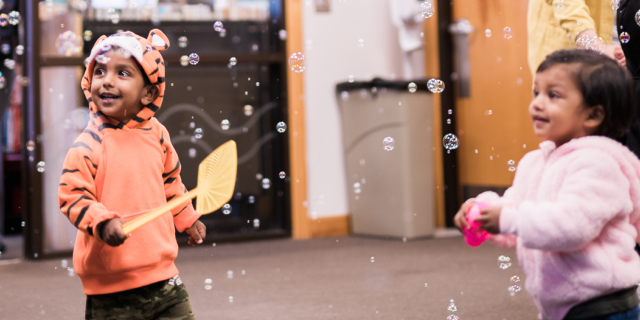 Young boy and girl popping bubbles with a fly swatter