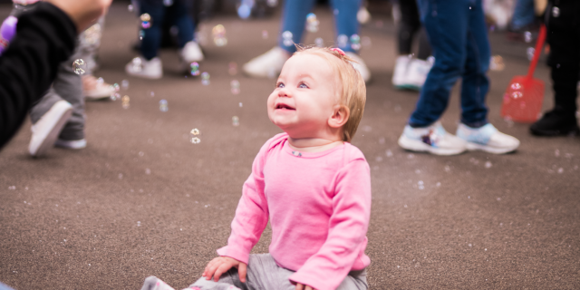 A baby very excited about bubbles around her