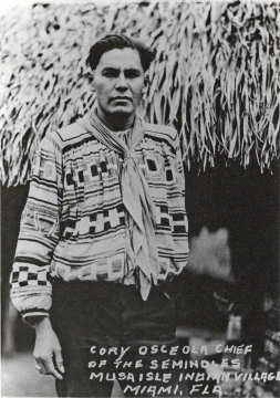 "A black and white portrait of Cory Osceola with ""Cory Osceola Chief of the Seminoles, Musa Isle Indian Village, Miami, Fla."" written on it"