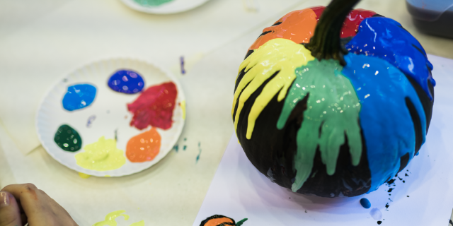 A pumpkin covered in different colors of paint