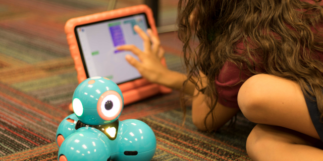 Girl programming a robot on a tablet