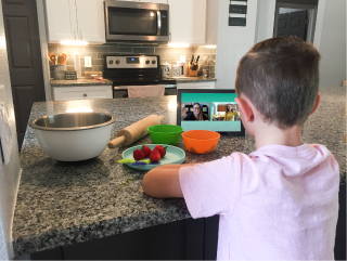 Boy watching a virtual kids cooking event on the Ipad sitting at the kitchen counter.