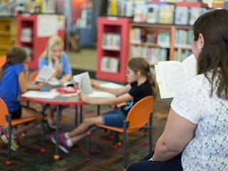 Adult with white shirt, hair clipped back is reading a chapter books with three young girls. Young girls are sitting on orange chair at a round table holding books.
