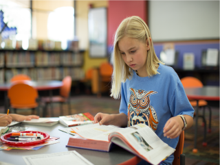 Girl with blue t-shirt reading at a table in the library