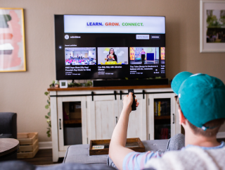 Photo of young man holding up a remote in front of TV in a living room with the library's YouTube channel on-screen.