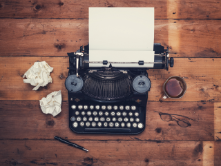 Overhead photo of typewriter on wooden background with crumpled papers and coffee cup
